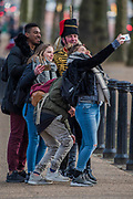 A Colour Sargeant in charge of the guides has time for a selfie with tourists as he waits for the Troop to arrive - The King's Troop Royal Horse Artillery, ride their horses and gun carriages past Buckingham Palace to Green Park to stage a 41 Gun Royal Salute to mark the 66th Anniversary of the Accession of Her Majesty The Queen.