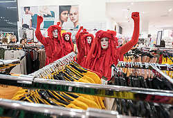 "© Licensed to London News Pictures. 01/06/2019. Bristol, UK. Extinction Rebellion's ""Redwatch"" protest inside Primark at Bristol's Broadmead shopping centre. Campaigners from Extinction Rebellion are carrying out a five-hour protest which will include everything from a 'pop-up' catwalk to blocking the city centre traffic. The protest targets Bristol's fashion and clothes stores with people urged to not buy any new items of clothing for the next year. There will also be a 'pop-up catwalk', where designers will be showing off their work to demonstrate the needed shift away from fast fashion towards a fairer, safer, cleaner, more transparent fashion industry. People are encouraged to repair, re-use, alter, upcycle and recycle clothes in a year-long boycott aiming to economically disrupt the fashion and textile industry demanding that it drastically changes the way it currently exploits people and planet for profit. The protest is part of a series of disruptive activities planned by Extinction Rebellion to highlight the fashion industry's contribution to climate change, biodiversity loss and environmental pollution. Photo credit: Simon Chapman/LNP."