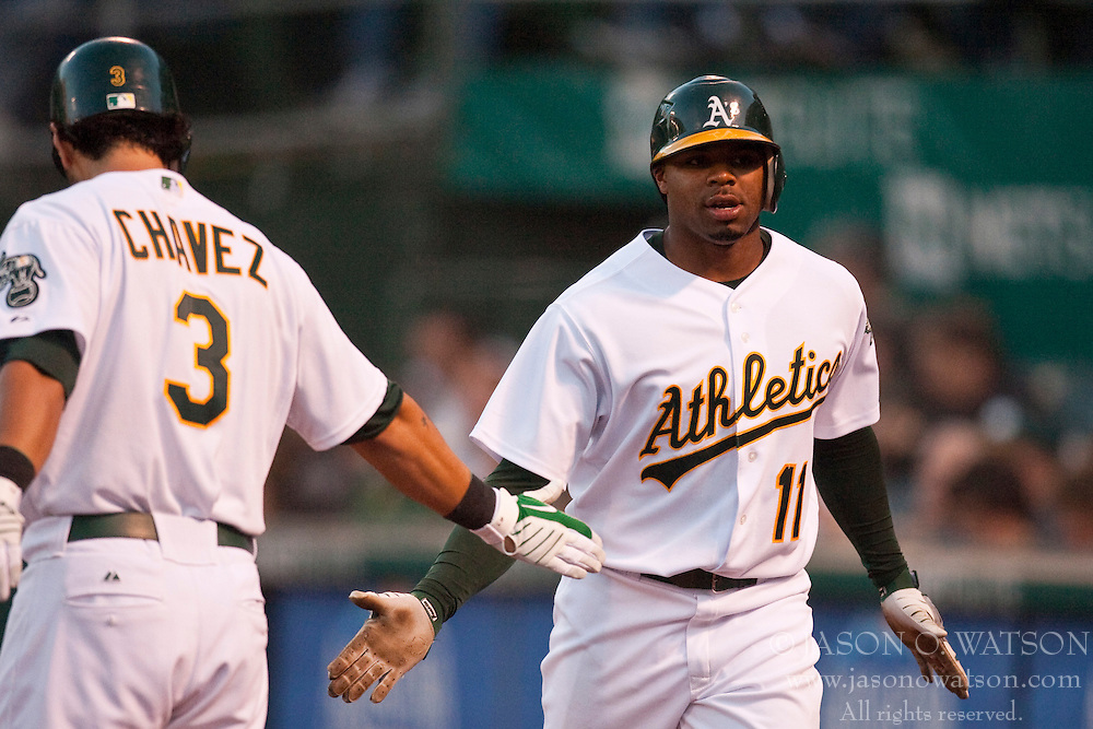 May 4, 2010; Oakland, CA, USA;  Oakland Athletics center fielder Rajai Davis (11) is congratulated by designated hitter Eric Chavez (3) after scoring a run against the Texas Rangers during the second inning at Oakland-Alameda County Coliseum. Oakland defeated Texas 7-6.