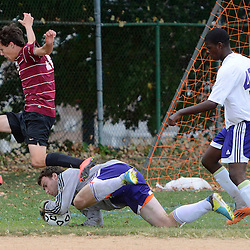 Radnor's Peter Cooke (12) leaps over Upper Darby's diving goal keeper Jonathan Thornton (44) in the first half during the Radnor at Upper Darby boys soccer game in Upper Darby Tuesday September 9, 2014. (Times staff / TOM KELLY IV)