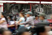 D Hai Ba Thrung. Motorcycle rushhour, OMO billboard. Man waiting at a bus station.