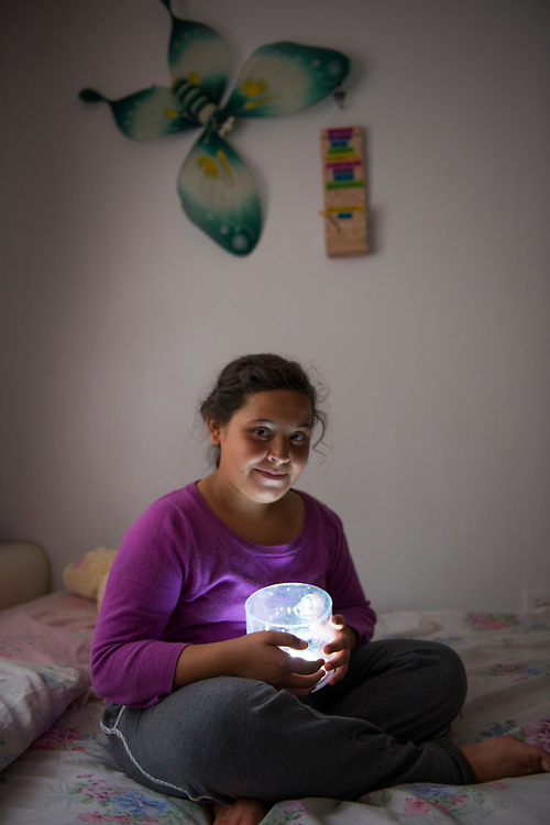 Vegas Abajo, PR, November 10, 2017--Adrianna Vera, 10, holds a solar lamp she received from Casa Pueblo. Adrianna mother says that Adrianna sleeps with the light on at night and it has helped her feel less anxious, which helps her adjust to the difficult life with no water or electricity since Hurricane Maria hit Puerto Rico September 20, 2017.  Casa Pueblo has become a center for relief operations and ramped up the campaign @LightupPRcasapueblo which distributes and promotes the use of solar energy in Puerto Rico. Casa Pueblo has distributed over 6,000 solar lamps since the storm. Photo by Lori Waselchuk/braf.org