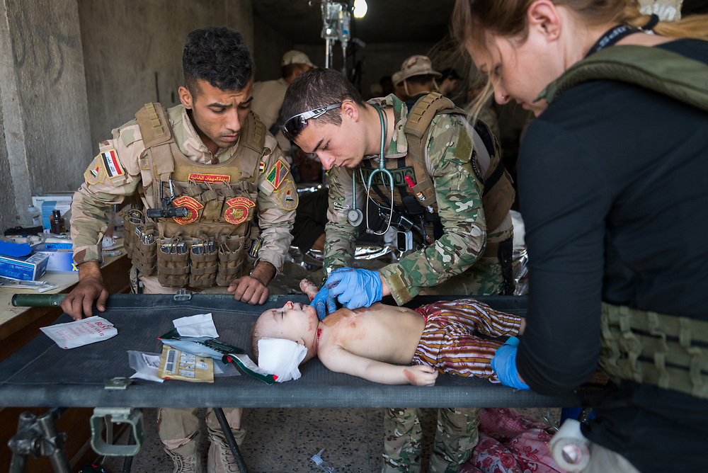 A baby with a shrapnel wound to his neck is treated by volunteer medics from international medical NGOs Academy of Emergency Medicine and Global Response Management at a makeshift field clinic on the edge of Mosul's Old City, Iraq, on June 23, 2017.<br /> <br /> As the fighting intensified to liberate the remaining pocket of ISIS-held territory in Mosul, civilians who had been held hostage inside the Old City risked their lives to escape, under fire from ISIS snipers.