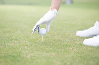 Cropped image of woman placing ball on golf tee
