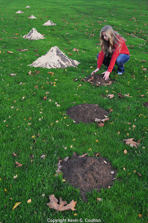 "Humorous photograph of a girl forming molehills into miniature mountains,visually depicting the saying ""Stop Making Mountains Out of Molehills!"""