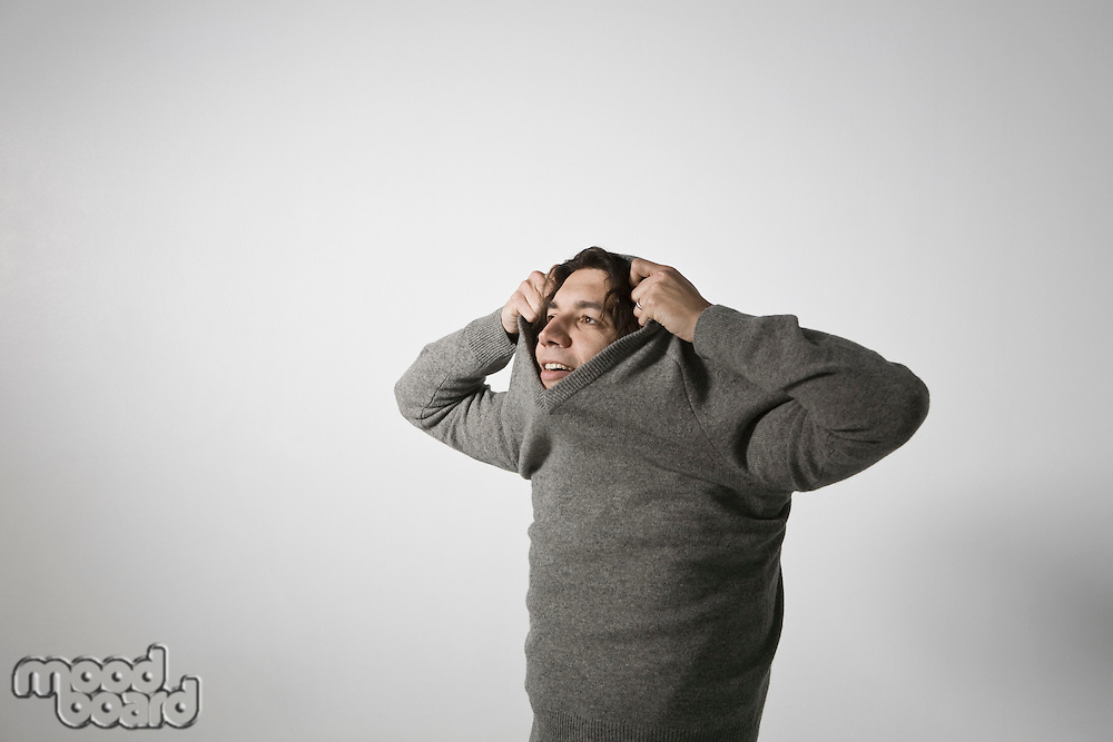 Mid-adult man pulling sweater over head