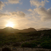The sun is setting down behind mountains in Charco del Palo, Lanzarote.