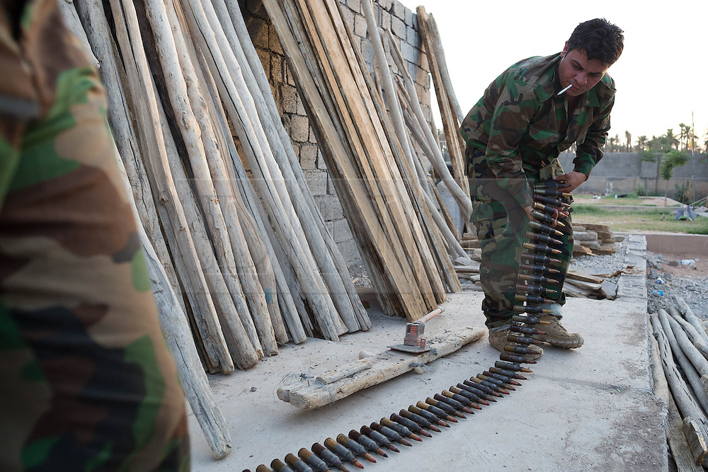 © Licensed to London News Pictures. 29/06/2014. Khanaqin, UK Khanaqin, Iraq. Kurdish peshmerga fighters prepare ammunition for a 14.5mm NSV heavy machine gun at a Kurdish peshmerga base in Khanaqin, Iraq. Counted by Kurds as part of their homeland, fighting in the nearby town of Jalawla now consists of occasional skirmishes and exchanges of fire between snipers and heavy machine guns on both sides.<br /> <br /> <br /> The peshmerga, roughly translated as those who fight, is at present engaged in fighting ISIS all along the borders of the relatively safe semi-automatous province of Iraqi-Kurdistan. Though a well organised and experienced fighting force they are currently facing ISIS insurgents armed with superior armament taken from the Iraqi Army after they retreated on several fronts. Photo credit : Matt Cetti-Roberts/LNP