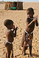 Two young Himba children playing, Namibia, Africa. Wall art and fine art photography for sale, stock images.