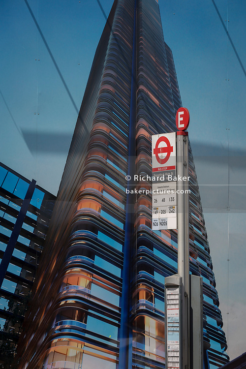 A bus stop sign beneath a construction hoarding showing the Foster-designed Principal Tower that's under construction on  Shoreditch High Street, on 10th May 2017, in London, England.