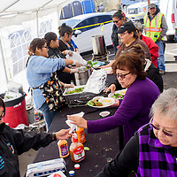 Guest line up to receive healthy and traditional foods during a harvest fest and farmers market outside Bashas Market in Window Rock Wednesday.
