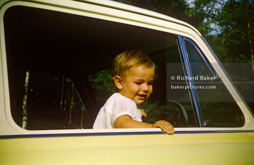 A young boy stands up in his father's Anglia car on a summer day out in the early nineteen sixties.