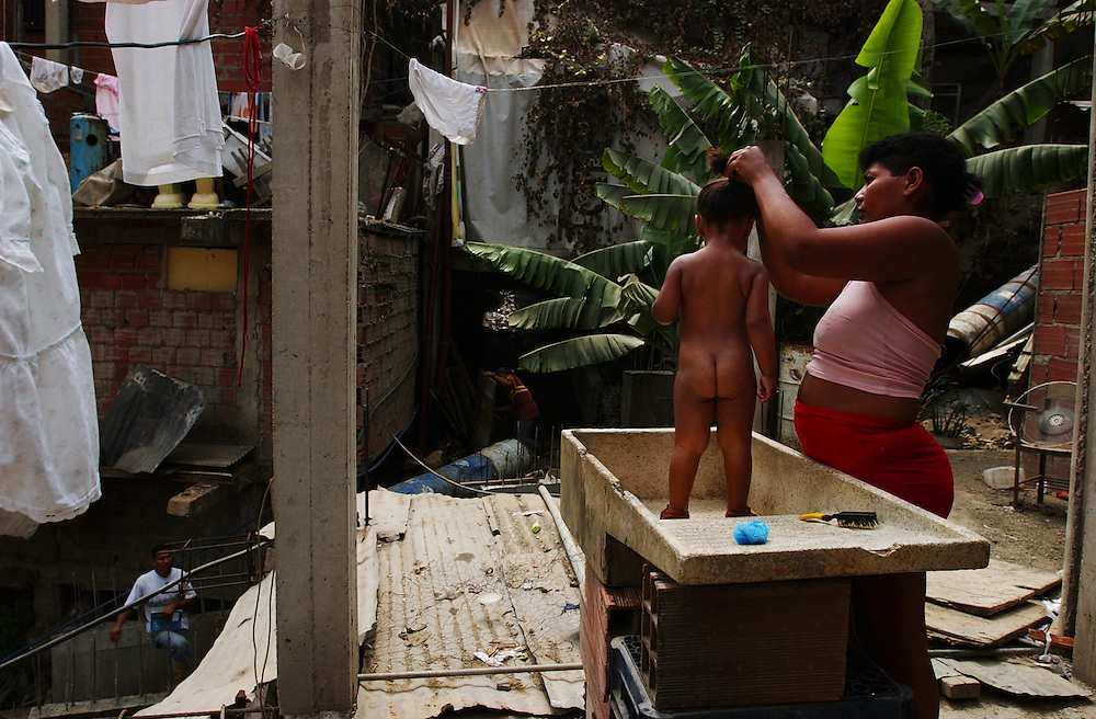 Carmen Alicia Castillo bathes her daughter Carla Joana.  Nearly two months after a national strike devastated Venezuela's economy, many people are still unable to find work.  Venezuela has a poverty rate of 80%.