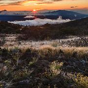 The winter sun sets over the Mauna Kea Volcano on the Big Island of Hawaii.