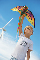 Boy (7-9) playing with kite at wind farm