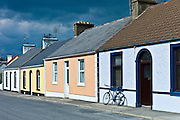 Street scene  pastel painted terraced bungalows and bicycle in Railway Road, Kilkee, County Clare, West of Ireland