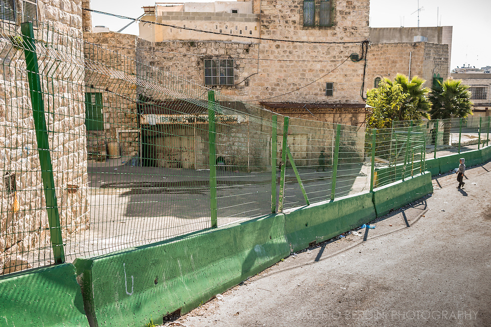 A Palestininian child walks through the barrier that limits the Arab part of Hebron city centre, from the Jewish-only area. Children are the only ones marginally allowed to walk beyond.