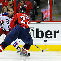28 April 2009:   New York Rangers center Scott Gomez (19) fires a pass in front of the goal against Washington Capitals defenseman Milan Jurcina (23) in the 2nd period in the seventh game of the Eastern Conference NHL quarterfinal playoff game at the Verizon Center in Washington, D.C.  The Washington Capitals defeated the New York Rangers 2-1 in the Eastern Conference NHL quaterfinal playoff to advance to the second round of the playoffs.