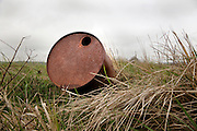 rusty barrel between tall grass in rural agricultural environment