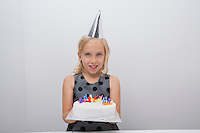 Portrait of cute girl holding birthday cake at home