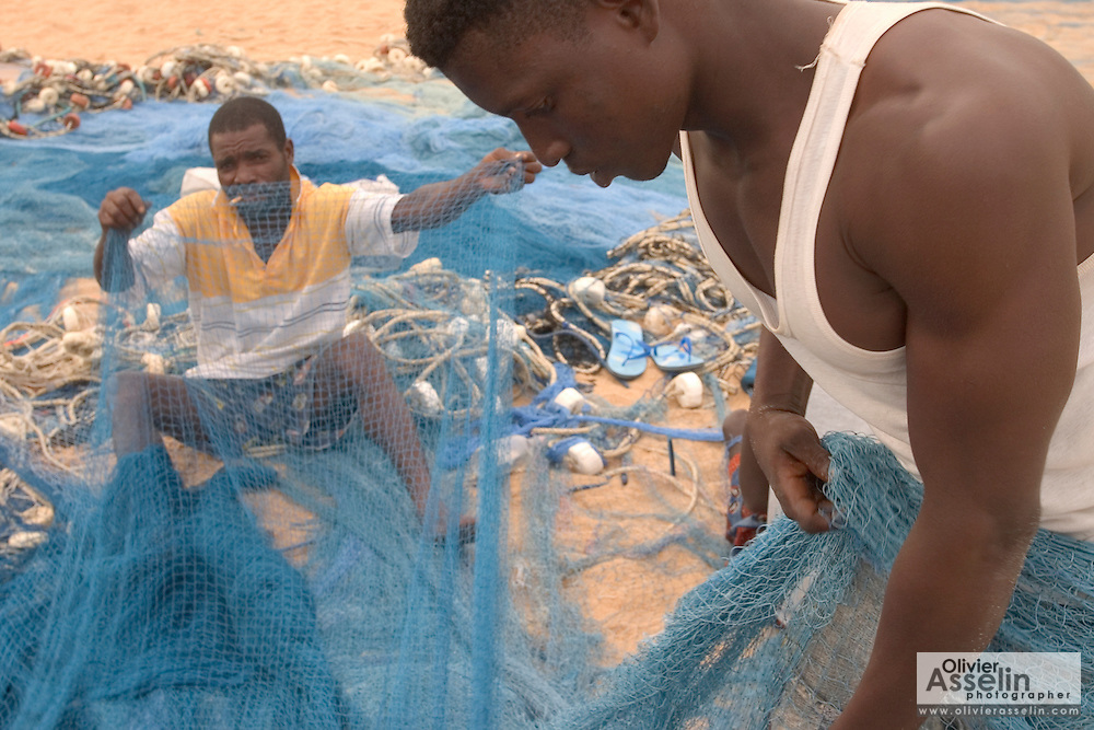 Fishermen repairing fishing nets on the beach at Aflao, Volta region, Eastern Ghana.