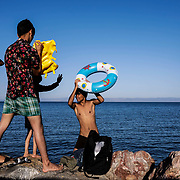 Migrants hang out on a beach located the outskirts of Moria camp as they, many from Afghanistan and Sub-Sahara Africa, remain trapped in squalid living conditions at camp on Lesvos Island in Greece onSaturday, September 28, 2019. Credit: Byron Smith