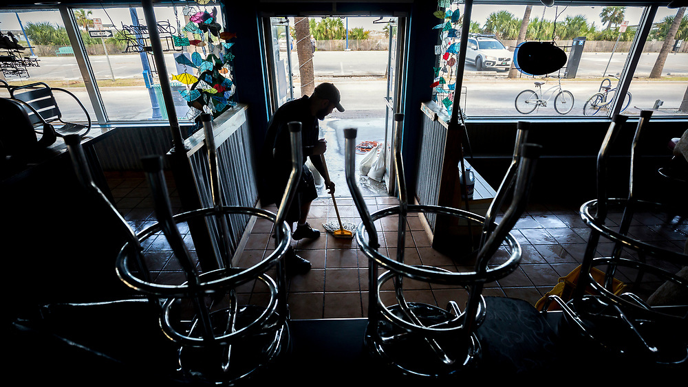 Fannie's By The Sea Manager Chris Jackson mops up his flooded restaurant, , Tuesday, Sept., 12, 2017, on Tybee Island, Ga., after Tropical Storm Irma flooded parts island. (AP Photo/Stephen B. Morton)