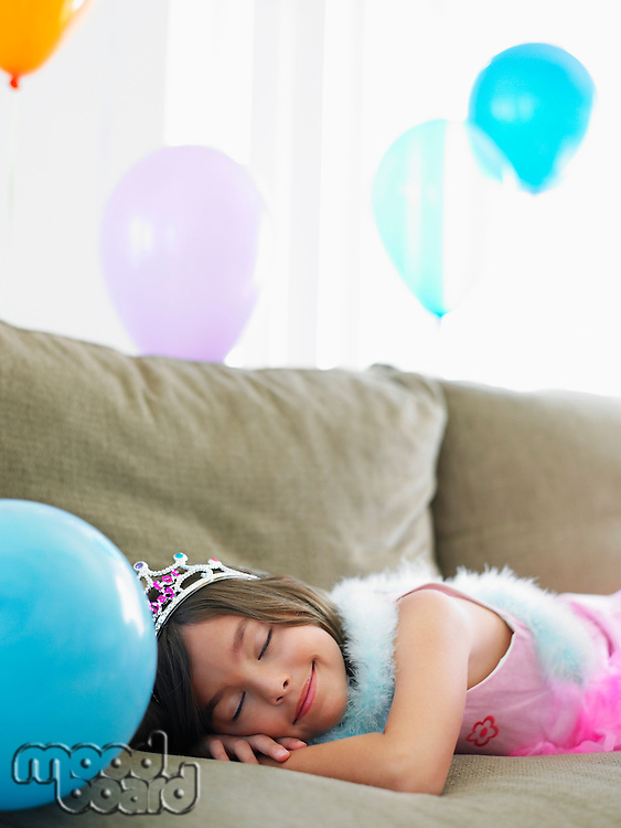 Young girl (7-9) sleeping on sofa with balloons