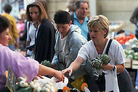 June 1996, Bergerac, France --- woman buying artichokes at Bergerac Saturday Market --- Image by © Owen Franken