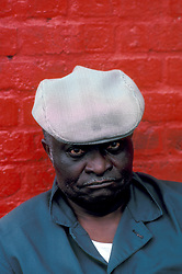 Portrait of African American Man Wearing Hat  in Front of Red Brick Wall