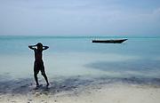 A young boy waits by his fishing boat on Nungwi Beach..Zanzibar, Africa.© Demelza Cloke