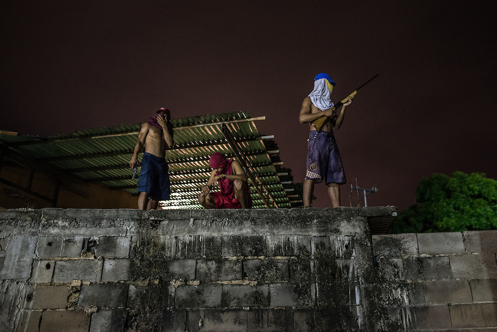 BOLÍVAR, VENEZUELA - DECEMBER 21, 2016: Gang members pose for a portrait while keeping a lookout for police and rival gangs in the slum where they live in Bolívar state in Eastern Venezuela.  Their gang is financed by robberies and selling drugs. Members of the gang say they cannot earn a living wage working regular jobs because of inflation.  A severe economic crisis in Venezuela, caused by the drop in oil prices and years of economic mismanagement under a Socialist government, has lead to an alarming rise in crime and insecurity in the country.  Hyperinflation has left both the working class and professional class of workers with salaries that cannot purchase enough food to feed their families for the month.  Many people are turning to crime to make ends meet.  PHOTO: Meridith Kohut for The New York Times