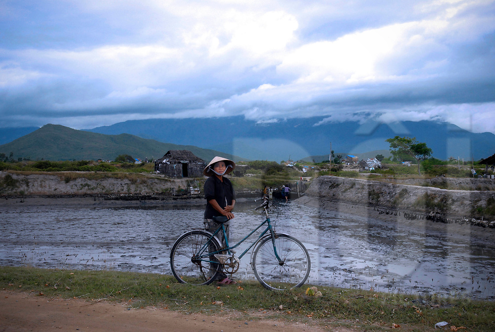 Vietnamese woman stands with her bicycle along a side road, Khanh Hoa province, Vietnam, Southeast Asia