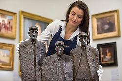 "© Licensed to London News Pictures. 16/11/2018. LONDON, UK. A technician examines ""Sil, Pater and Ned"", 2000, by Rowan Gillespie (Est. GBP18,000-20,000). Preview of ""A Living Legacy"", the Irish Art Collection of Brian P. Burns, a collection spanning artists from the 18th century to the present day.  Over 100 works will be offered for sale on 21 November at Sotheby's in London.  Photo credit: Stephen Chung/LNP"