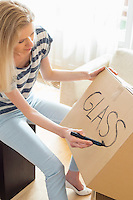 Woman labeling moving box with glass material at home