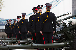 © Licensed to London News Pictures. 21/04/2014. London, UK. Members of the Honourable Artillery Company (HAC) stand in front of light guns as they prepare for a 62 Gun Salute in honour of Her Majesty the Queen's 88th birthday today, 21st April 2014 at the Tower of London in front of Tower Bridge in London.. Photo credit : Vickie Flores/LNP