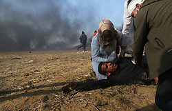 Medics treat a Palestinian woundedman during clasheswith Israeli soldiers at the border fence with Israel east of Khan Yunis in the southern Gaza Strip, Israeli soldiers killed at least 60 Palestinians and wounded more than 2,700. as demonstrations on the Gaza-Israel border coincided with the controversial opening of the U.S. Embassy in Jerusalem. This marks the deadliest day of violence in Gaza since 2014. Gaza's Hamas rulers have vowed that the marches will continue until the decade-old Israeli blockade of the territory is lifted. Gaza Strip, Palestine, May 15, 2018. Photo by Ashraf Amra/SalamPix/ABACAPRESS.COM
