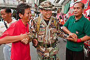 "May 12 - BANGKOK, THAILAND: Maj. Gen. KHATTIYA ""Seh Daeng"" SAWASDIPOL (CENTER) greets civilian supporters in the Red Shirt camp in Bangkok Wednesday. Seh Daeng, as he is known, has emerged as the Red Shirts unofficial military commander. He has organized the barricades that ring the Red Shirt camp and has threatened to organize a guerilla campaign against the government if the Red Shirt protest is crushed by force. Seh Daeng is a hero to many Thais because he is credited with crushing Thailand's communist insurgency in the 1970's and 80's. He was the commander of Thailand's Internal Security Operations Command but after his political activities became apparent he was made the head aerobics instructor for the Thai army. He is now seen as one of the major personalities destabilizing the country and the government alleges that he is behind many of the grenade attacks and drive by shootings directed at government buildings and officials and he is wanted for a long list of felony offenses including weapons charges and terrorism related charges. Although some Red Shirts have officially repudiated him, he is still frequently seen around the Reds' barricades. The army has started proceedings to fire him, but he remains a general on active duty.   Photo by Jack Kurtz"