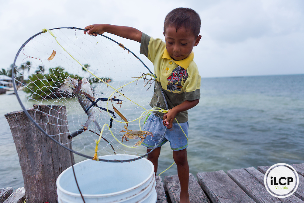 Jhoan Balam, one of the very few children living in the small, remote fishing camp of Punta Herrero in the Sian Ka'an Biosphere Reserve in southernmost Caribbean Mexico, tends crab pots on the dock. From a 2014 iLCP (International League of Conservation Photographers) expedition project documenting the people and places of the Mexican section of the Mesoamerican Reef (MAR).