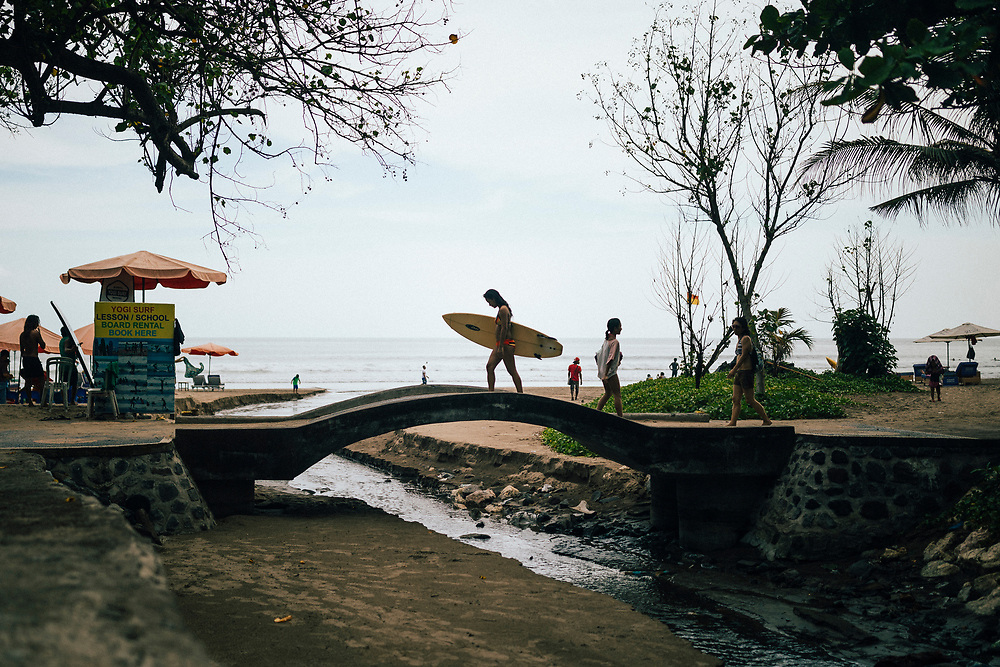 A surfer carries her board over a small bridge near Seminyak beach in Bali, Indonesia.