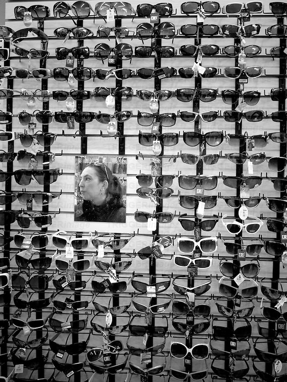 a hispanic woman at a five & dime gift shop is reflected in a mirror surrounded by a wall of sunglasses.  vertical composition taken in santa fe, new mexico.