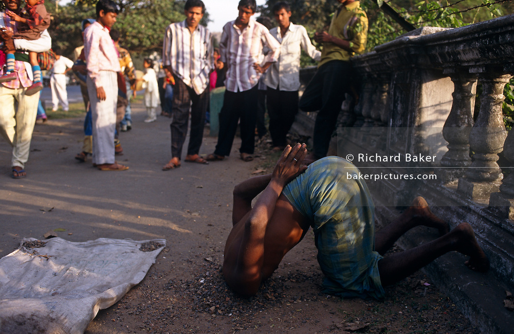 A holy Sadhu man attracts a crowd on the Maidan in central Calcutta, India. Near some ballustrades built by the British during the last years of the Raj, the man is leaning forward on his knees and his head is buried in gravel. Practicing Tapas or Niyamas, is one form of Austerity that holy men like this perform to cleanse themselves of bad thoughts. It is a conservation of energy; an increase of power in the system by sense control; a process of positive-thought, self-imposed  hardships and inner-strength - all to gain a higher being for oneself. They might stand in cold water in winter, stand on or bury their heads in earth. Niyamas also breeds non-violence, truthfullness, non-stealing, moderation, non-possessiveness, purity, contentment, discipline, study and surrender.