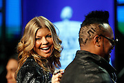 Female vocalist for The Black Eyed Peas, Stacy Ann Ferguson, better known as Fergie (left), points out the Super Bowl XLV logo cut into the hair of fellow Black Eyed Peas member Allan Pineda Lindo Jr., better known as apl.de.ap, while addressing the media at the Super Bowl XLV Halftime Show press conference featuring The Black Eyed Peas (held during the week of NFL Super Bowl XLV between the Pittsburgh Steelers and the Green Bay Packers) on Thursday, February 3, 2011 in Dallas, Texas. ©Paul Anthony Spinelli