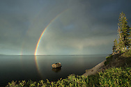 Prior to the onset of a series of spring thunderstorms, a double rainbow appears above Yellowstone Lake. The calm didn't last long, as the dark sky and stormy light foretold of the heavy rains just a few moments away.