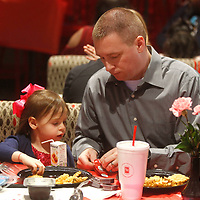 Len Fortenberry, of Saltillo, opens a pack of ketchup for his daughter Brooke, 3, as they start their meal together at Chick-fil-a's Daddy Daughter Dinner Tuesday night in Tupelo. This was their first time to attend the dinner.
