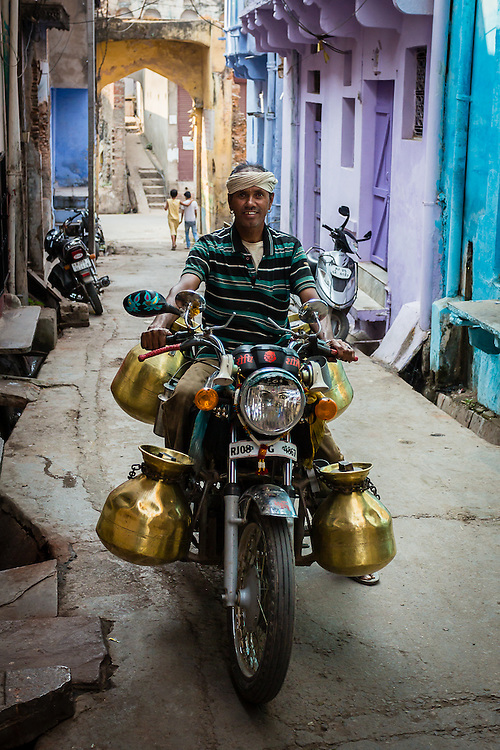 A milkman rides his motorbike through the narrow streets of Bundi. Milkmen usually sell milk in the early morning. They either stope at people's doors or at specific places where the people come and meet them.