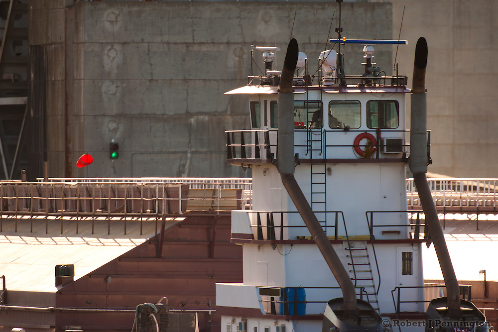 A river tug pushes a barge upstream to a set of locks.