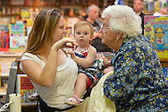 Huntington, New York, U.S. - August 6, 2014 - A young mom holding a baby girl and a senior woman talk while waiting online at the book signing for the Hillary Clinton new memoir, Hard Choices, at Book Revue in Huntington, Long Island.