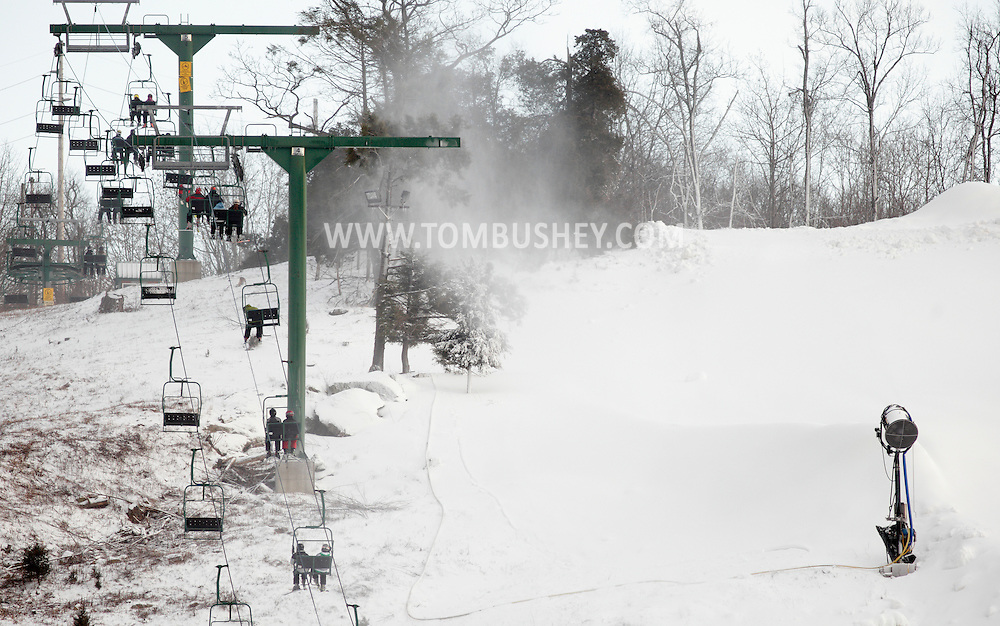 Warwick, New York - Skiers ride up a lift as snow-making machines work to cover the slopes at Mount Peter ski area on Dec. 17, 2010.