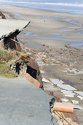 Concrete flooring and roadway abruptly ending at eroded cliff edge at Tunstall; East Yorkshire; England